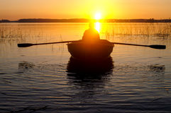 Boating. Man swimming in a boat at sunset Stock Images