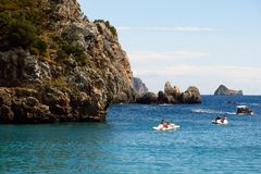 Boating in Mediterranean Sea off coast of Corfu Greece. Corfu, Greece - September 3, 2014: People on pedal boats and sightseeing boats enjoy a blue bay on the Royalty Free Stock Image