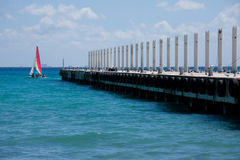 Boating at Playa Del Carmen, Mexico. A sailboat at the end of the pier stock image
