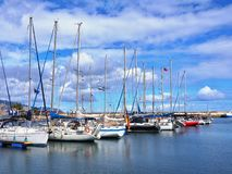 Boating port with larger sailboats lying in front of Santa Cruz de Tenerife, Canary. The sky is full blue with white clouds, bright friendly image in diagonal royalty free stock images