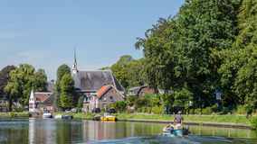 Boating on the river Vecht along the church of Zuilen near Utrec Royalty Free Stock Images