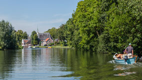 Boating on the river Vecht along the church of Zuilen near Utrec Stock Image