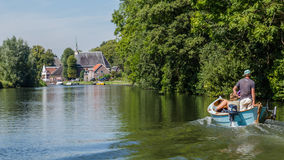 Boating on the river Vecht along the church of Zuilen near Utrec Stock Photo
