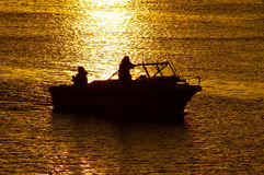 Boating at sunset. A boat coming into the harbor, as the water reflects golden light of sunset Royalty Free Stock Image