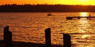 Boating at Sunset. A boat passes by the docks at Marina Park in Kirkland, Washington Stock Photos
