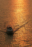 Boating at sunset. Boating in waters reflecting the colors of the sunset Stock Photo
