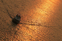 Boating at sunset. Boating in the reflected colors of the sunset Stock Image