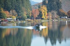 Boating on Triangle Lake, Oregon. A speed boat races across the calm surface of an autumn reflection on Triangle Lake, Oregon stock image