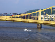 Boating Under The Bridges. A Motor Boat Traveling Under A Bridge In Pittsburgh Royalty Free Stock Photography