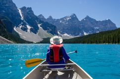 Boating on the uniquely blue waters of Moraine Lake. Woman with colorful white hat, navy blue coat and red life vest paddling a canoe set against the glaciers stock image