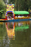 Boatman poling brightly colored boat Royalty Free Stock Photos