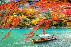 Boatman punting the boat at river. Arashiyama in autumn season along the river in Kyoto, Japan.  Stock Photo