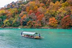 Boatman punting the boat at river. Arashiyama in autumn season along the river in Kyoto, Japan. KYOTO,JAPAN - NOVEMBER 16 : Boatman punting the boat at river Stock Photography