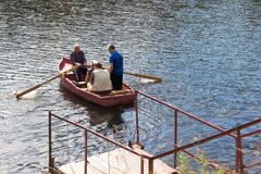 Boatman transporting people across the river. DMITROV July 01: Boatman transporting people across the river for a fee on 1 July 2015 in Dmitrov in Russia Royalty Free Stock Photography