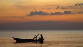The boatman in the Vietnamese hat in the small boat. The man fishes at sunset. Close up. Silhouette at sunset.View from. On this video you can see as the small stock video