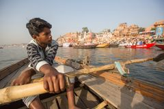Boatmen on a boat glides through water on Ganges river along shore of Varanasi. Stock Photo