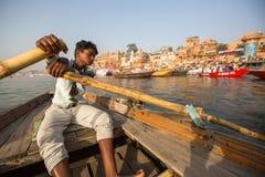 Boatmen op een boot glijdt door water op de rivier van Ganges langs kust van Varanasi Stock Foto's