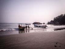 Boatmen waiting with their boat in the beach stock images
