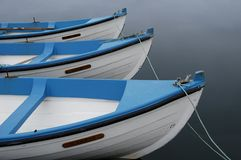 Boats. Three boats on calm water. Blue and white wooden row boats stock photo