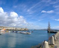 Boats. In blue waters with pier and lighthouse in distance in Dun Laoghaire Harbour, Ireland Stock Photos
