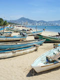 Boats on Acapulco shore. ACAPULCO, MEXICO - MARCH 11, 2006 : A group of boats lined up on the beach with people in the background in Acapulco, Mexico royalty free stock photo