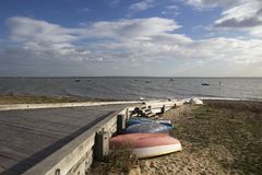 Boats against a wooden jetty on Jubilee Beach, Southend-on-Sea,. Colourful boats against a wooden jetty on Jubilee Beach, Southend-on-Sea, Essex, England Stock Photos