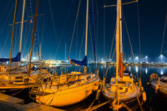 Boats in Alghero harbor at night Stock Image