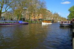 Boats on Amsterdam Canal River - Netherlands Stock Photo