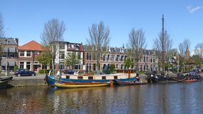 Boats are anchored along a canal wall in a Dutch city. Several boats lie at anchor at a canal side on a sparkling sunny day in a northern Dutch city royalty free stock photos