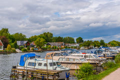 Boats anchored on the bank of the river, residential houses on t Royalty Free Stock Photos