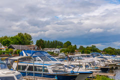 Boats anchored on the bank of the river, residential houses on t Stock Images