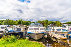 Boats anchored on the bank of the river, residential houses on t Stock Image