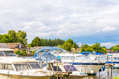Boats anchored on the bank of the river, residential houses on t Royalty Free Stock Photo