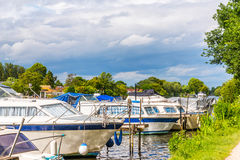 Boats anchored on the bank of the river, residential houses on t Stock Photo