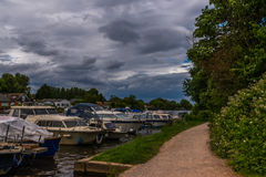 Boats anchored on the bank of the river, residential houses on t Stock Photography