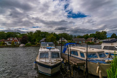 Boats anchored on the bank of the river, residential houses on t Stock Photos