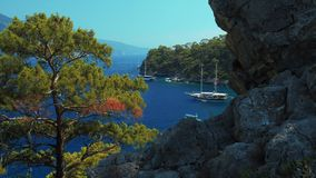 Boats anchored in a blue lagoon. View from the coast with rocks and trees. Fethiye, Turkey. Set of four clips stock footage