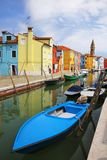 Boats anchored in canal in Burano, Venice, Italy. Burano is an island in the Venetian Lagoon and is known for its lace work and brightly colored homes stock photos