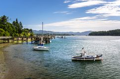 Boats Anchored in a Harbour on a Clear Summer Morning. Boats Anchored in a Harbour at Low Tide with Wooden Piers in Background on a Clear Summer Morning. Sooke royalty free stock photography