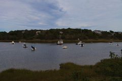 Boats anchored in a quaint Cape Cod waterway Stock Images