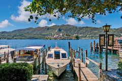 Boats ancored along wooden pier on Lake Orta in Italy. ORTA SAN GIULIO, ITALY - AUGUST 12, 2017: Boats anchored along small wooden pier on Lake Orta - famous Stock Photo