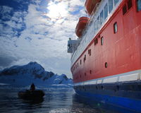 Boats in Antarctica. Big ship and small Zodiaс boat in Antarctica, men in the boat in Antarctica Royalty Free Stock Image