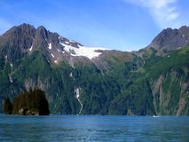Boats Appear Small Besides Chugach. Boats appear tiny compared to the towering majesty of the Chugach Mountains. Anderson Glacier and Anderson Waterfall can be stock photo