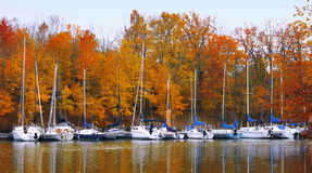 Boats in autumn. Rich autumn colors explode at the end of the sailing season Royalty Free Stock Photo