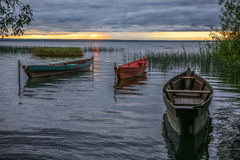 Boats on an autumn decline. Three wooden fishing boats on an autumn decline at the coast of the lake Stock Photos