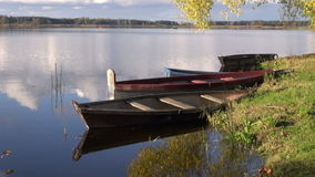 Boats on autumn lake and reflections stock video