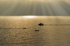 Boats backlit cross at sunset Stock Images