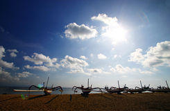 Boats on Bali beach. A photograph image of a row of traditional old style sailing or fishing boats with bamboo stabilisers, just as those found on outriggers Stock Images