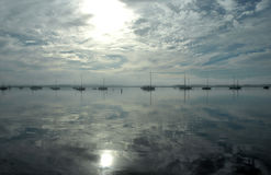 Boats on the Bay. A glassy bay reflects the sun, sky and sailboats Stock Photo