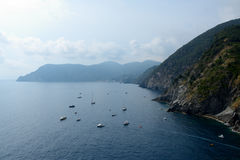 Boats in bay and high cliff in Vernazza, Italy Royalty Free Stock Photo